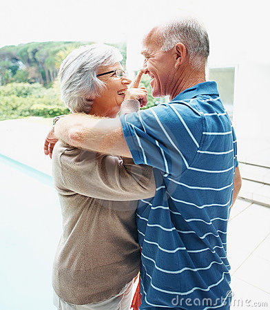 Senior couple having fun by a swimming pool