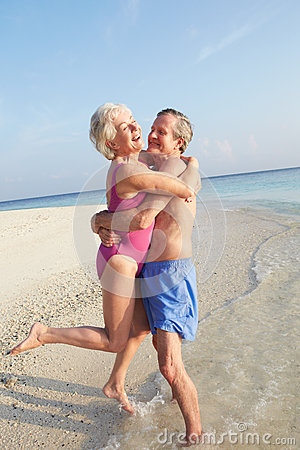 Senior Couple Having Fun On Tropical Beach Holiday