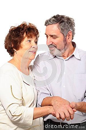 Senior couple hold for hands, hug
