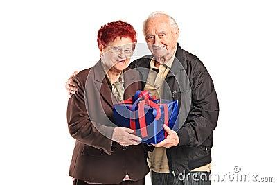 A senior couple holding a gift