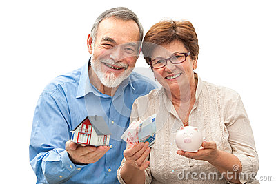 Senior couple holding a house model and piggy bank