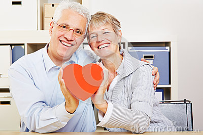 Senior couple holding a red heart