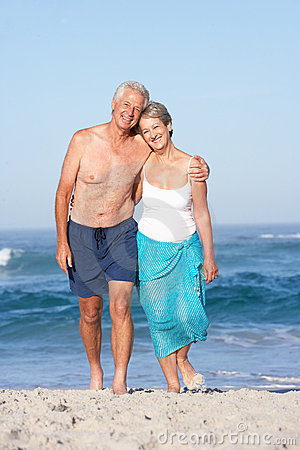 Senior Couple On Holiday Walking Along Sandy Beach