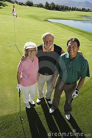 Senior couple with instructor on golf course