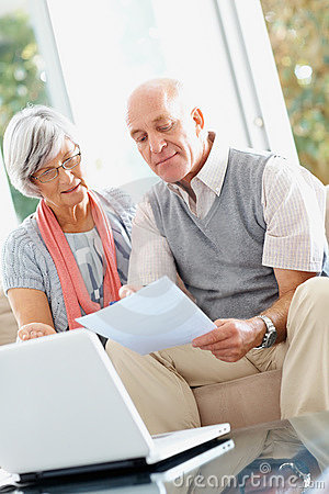 Senior couple with laptop reading a document