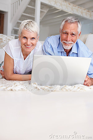Senior couple lying on bed with laptop in front