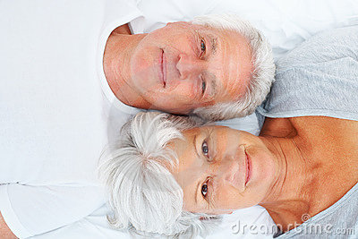 Senior Couple Lying Together On Bed Stock Photography - Image: 21277872