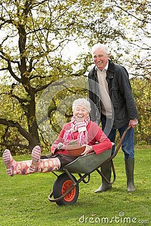Senior Couple Man Giving Woman Ride In Wheelbarrow
