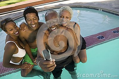 Senior couple and mid-adult couple posing for mobile phone photograph at swimming pool elevated view.
