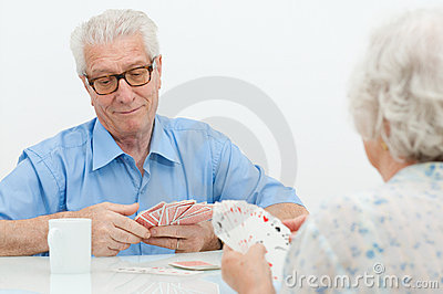 Senior couple playing with cards