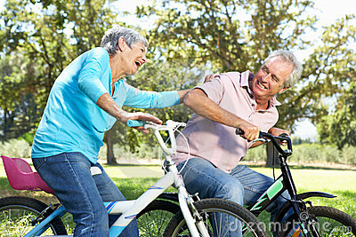 Senior couple playing on children s bikes
