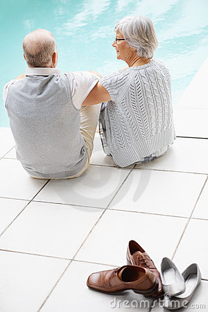 Senior couple by pool with footwear in foreground