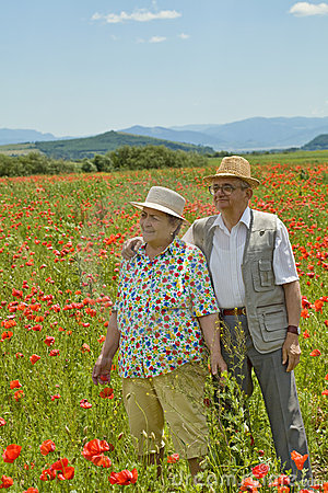 Senior couple on poppy field in early summer