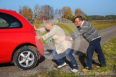 Senior couple push the broken car