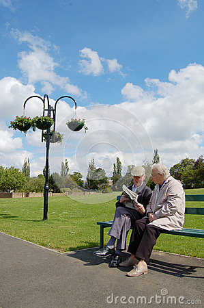 Senior couple reading newspaper on a park bench