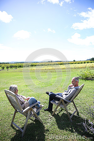 Senior couple relaxing in chairs on sunny day