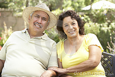 Senior Couple Relaxing In Garden Together