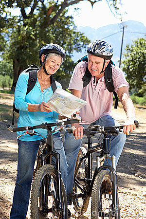 Senior couple riding bikes looking at a map