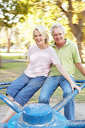 Free Senior Couple Riding On Roundabout In Park Stock Photo - 14639920