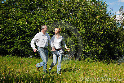 Senior Couple running on a meadow