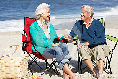 Senior Couple Sitting On Beach Having Picnic