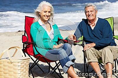 Senior Couple Sitting On Beach Having Picnic