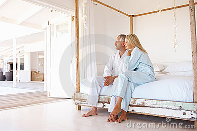 Senior couple sitting on the bed, looking away