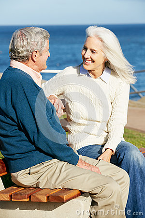 Senior Couple Sitting On Bench By Sea Together