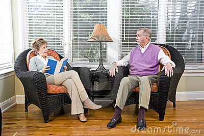 Senior couple sitting on living room chair reading