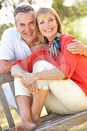 Senior Couple Sitting Outdoors On Bench