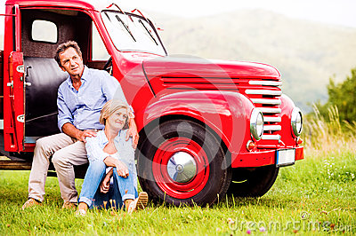 Senior couple sitting at the red vintage car Stock Photo
