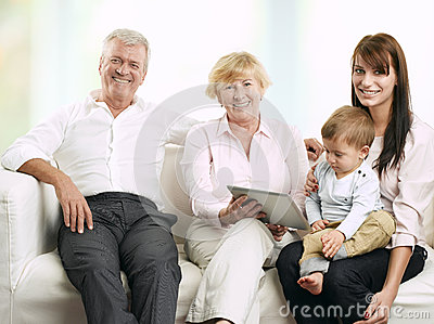 Senior couple sitting with their daughter and grandson