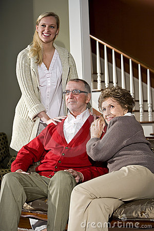 Senior couple on sofa at home with adult daughter