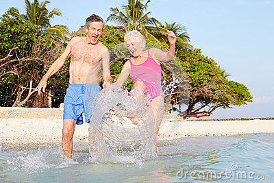 Senior Couple Splashing In Sea On Tropical Beach Holiday