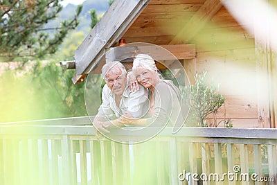 Senior couple standing on terrace on holdays Stock Photo