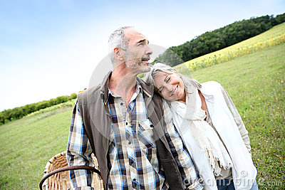 Senior couple standing together in fields