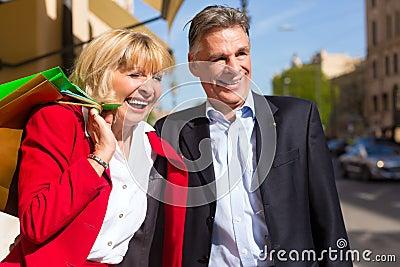 Senior couple strolling through the city shopping