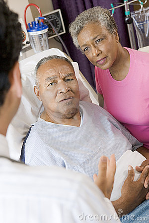 Senior Couple Talking To Doctor