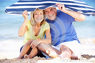 Senior Couple Under Beach Umbrella