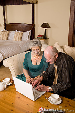 Senior couple using laptop in hotel room