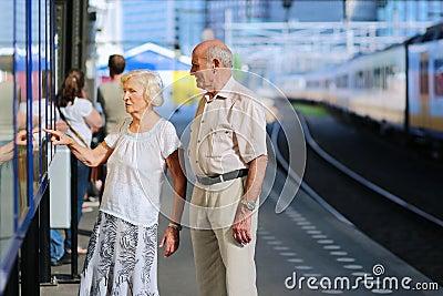 Senior couple waiting for train at railway station