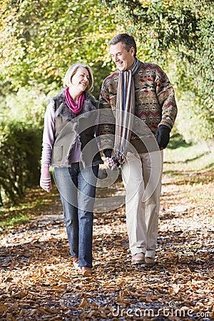 Senior couple walking along autumn path