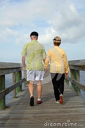 Senior couple walking back view