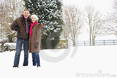 Senior Couple Walking In Snowy Landscape