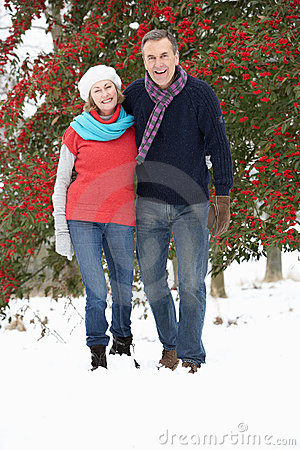 Senior Couple Walking Through Snowy Woodland