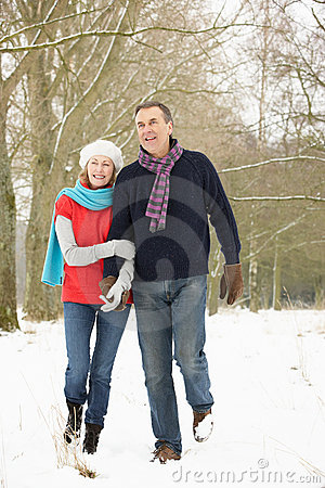 Senior Couple Walking Through Snowy Woodland