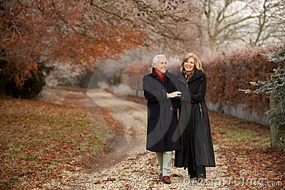 Senior Couple On Winter Walk Through Frosty Landsc