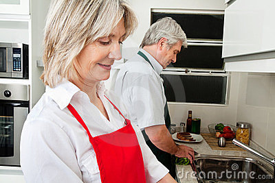 Senior couple working in kitchen