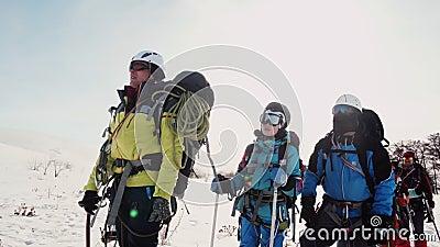 Senior des Teams der Bergsteiger zeigt die Richtung der Weghand mit einer Eis-Auswahl das Team hört auf ihn stock video footage