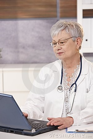 Senior doctor using laptop